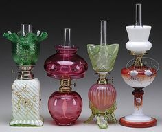 "This lot consists of an LG Wright cranberry with thumbprint pattern lamp, a cranberry opalescent stripe font with vaseline applied feet and vaseline swirl shade, a painted milk glass pedestal style base with white milk glass shade and a cased, swirl ribbed base with applied jewels and enamel decor topped with a diamond patterned ruffled top green shade. Assorted burners. SIZE: Ranges from 8-1/2"" to 10-1/2"" t. CONDITION: Generally good with the cranberry lamp being all orig..."