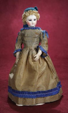 Petite French Bisque Poupee with Wooden Articulated Body, wearing a silk gown,undergarments,blue velvet cap,leather boots, circa 1867.