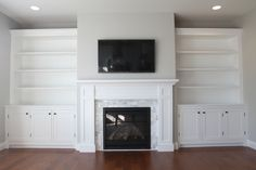 Custom white shaker style cabinets and fireplace surround. Corian marble facing, clean lines and simple design with large bookshelves cabinets and lighting in our living room