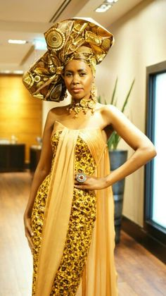 Gold form-fitting dress with floor length flowing chiffon material sown to left and right neckline. A fanned out traditional sculptured african head scarf crowns this stunning ensemble