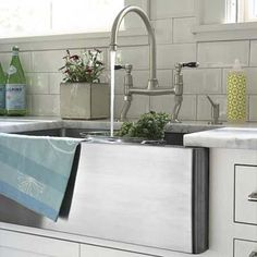 A deep farmhouse sink and faucet in stainless steel reinforces the updated traditional style of this kitchen space (while also hiding dirty dishes).