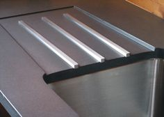 Stainless Steel Bars create a drainboard  Concrete Countertops -Trueform Concrete Custom Work