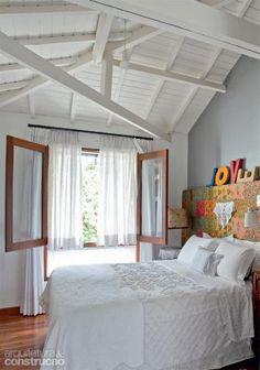 """O quarto do casal fica no piso superior da antiga edícula. """"Como mantive o telhado, instalei um forro de madeira sob o vigamento"""", explica a arquiteta. Projeto de Sandra Sayeg"""