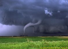 A ghostly white tornado snakes it's way out of a storm threatening Emmetsburg Iowa on June 11th, 2004.
