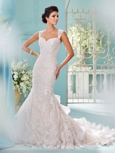 David Tutera for Mon Cheri - 216251 Mora - Tulle and organza over satin fit and flare gown with hand-beaded re-embroidered Alencon Lace appliqués, lace cap sleeves, Queen Anne neckline, lace appliqué illusion heart shaped back bodice with crystal button closures, tulle and lace appliquéd overskirt with front scalloped hem, circular cut organza ruffled inset back skirt and chapel length train.  Sizes: 0 - 20  Colors: Stone/Gardenia, Ivory White