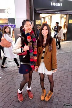 The girl on the right is wearing a mustard blazer with a bow pinned to it, a short knit top, a sheer white skirt, polka dot stockings & yellow leather boots.