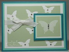 """I created a background of Bitty Butterfly punches for this card and adhered a small Basic Rhinestone into the center of each. As the punch would only reach so far, I actually used two pieces of Pistachio Pudding card stock joining them under the Whisper White 3/8"""" Taffeta Ribbon.     The larger butterfly was heat embossed with White Emboss Powder and layered onto Coastal Cabana and Island Indigo."""