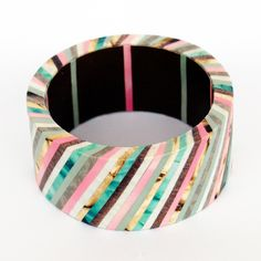Magazine paper, narrow strips of turquiose, pink, cream, beige, brown, grey, decoupaged bangles with dark brown and strips on the inside.  #DiyBangles