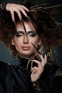 High fashion model in black dress, with long nails, creative hairstyling and makeup