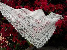 This triangle shawl is knitted from an edging. It begins with a long strip of lace edging. Then stitches are easily picked up from the yarn over loops along the edge and triangle body is worked.