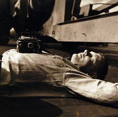 Lieutenant Commander Horace Bristol takes a short nap on the flight deck, but then his camera is strapped on and ready for instant action, TR-12985, February 1945. U.S. Navy Photograph, now in the collections of the National Archives.