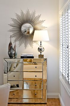 Highgate House    Beautiful mirrored chest of drawers topped with three glass vases, stacked books and a polished silver table lamp. A large silver sunburst mirror sparkles over the chest. Ivory colored walls pair with white plantation shutters and hardwood floors to complete the space.