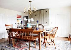 All wood dining room table and chairs, as well as large area rug and rustic wooden cabinets.
