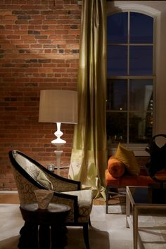 That exposed brick is fantastic.  and those dramatic draperies really help soften it up.