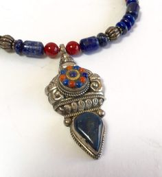 Handcrafted dark lapis bead necklace and sterling silver pendant with coral and lapis; necklace of shaped lapis beads - dark blue with red accents  $285 DianaKirkpatrick.com