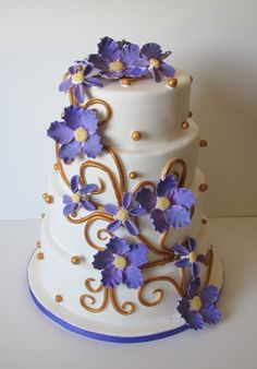 Stacked round tieres with purple gumpaste flowers and gold swirls and beads.
