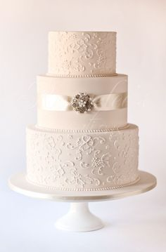 3 tier wedding cake with a vintage theme. Cake is iced in ivory fondant. Design is piped in white royal icing, with some brush embroidery,
