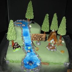 Camping and fishing cake for a 6 year old little boy,  Chocolate cake with raspberry filling covered in fondant  A black bear enjoying a hotdog and fish while the camper is sleeping inside the tent. there is a sleeping skunk at the top of the mountain.  everything is made out of fondant and gumpaste, trees are covered sugar cones with pretzel trunks  Thanks for looking