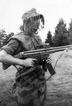 "A German infantryman armed with a StG 44, wearing ""splinter"" camouflage and a ghillie cap in 1944."