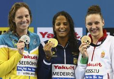 Emily Seebohm of Australia, Etiene Medeiros of Brazil and Katinka Hosszu of Hungary celebrates on the podium after the Women's 50m Backstroke Final during day five of the 12th FINA World Swimming Championships (25m) at the Hamad Aquatic Centre in Doha, Qatar.