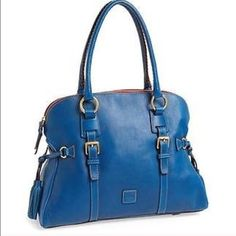 Dooney & Bourke blue domed buckle satchel Gorgeous Italian leather satchel bag is made of buttery soft pebbled leather in a rich shade of royal blue. Brass buckles and straps on front and back are as decorative as the tassel ties on either side. Lined in red fabric and a red fabric zipper (with brass zipper teeth), this provides a stunning contrast to the blue leather. The interior compartment is super roomy and has 2 pockets, a full zipper compartment, and key ring strap. Brand new with…