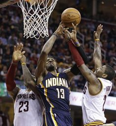 Indiana Pacers' Paul George (13) drives to the basket between Cleveland Cavaliers' LeBron James (23) and Kyrie Irving (2) in the first half of an NBA basketball game Monday.
