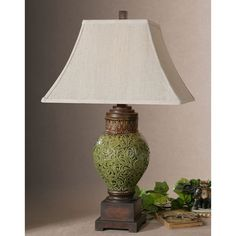 A heavily distressed crackled green lamp with rust brown details and burnished accents adds timeless charm to this lamp. The square top, rectangle bottom bell shade is a beige linen fabric.