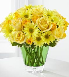 Spring flower arrangement with daisy and yellow roses and minis