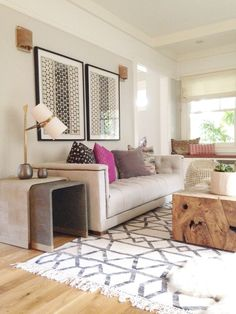 Geometric rug, large art, a statement table, and accents of pink & purple. Sophisticated & still playful.