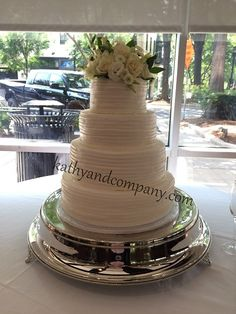 Piped ruffle buttercream wedding cake with fresh flowers on top.