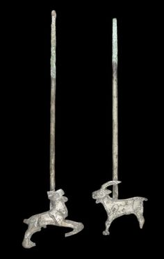 A pair of Urartian silver pins  Iran, circa 8th-7th Century B.C. Both with flat terminals depicting goats, with long curved horns and short beard, one standing and the other jumping forward, with added incised details, 5¼in-5¾in (13.5cm-14.5cm) long, mounted