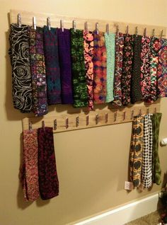 The Wall of LuLaRoe Leggings! Fun easy DIY project to organize leggings, skirts and more! Washi tape decorated clothespins mounted with Gorilla glue to upcycled floor boards from Habitat ReStore. Use several Command Strips to attach to wall. Easy to move, no damage!