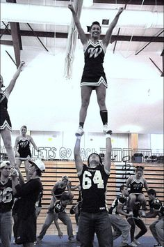 football players stunting with the cheerleaders! <3