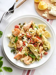 Shrimp Pasta with Roasted Red Peppers and Artichokes | foodiecrush.com: 12 ounces farfalle pasta (bow tie) or other pasta 1½ pounds fresh or frozen medium shrimp in shells ¼ cup butter 3 cloves garlic, minced 1 12-ounce jar roasted red bell peppers, drained and chopped 1 cup canned artichoke hearts in water or brine, quartered ½ cup dry white wine 3 tablespoons drained capers ½ cup whipping cream 1 teaspoon finely shredded lemon peel 2 tablespoons lemon juice ¾ cup crumbled feta cheese (3…