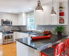 White Cabinetry Gray Subway Tile And Belgium Moon Quartz Countertops With Pops Of Red Accent