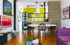 Sala de jantar com cozinha integrada, parede de concreto e cadeiras pretas.