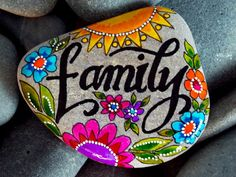 family. we are family. my tribe. sisters. brotherhood. team. happiness.  painted rock (sea stone) from Cape Cod.  This stone is very smooth and tumbled many years in the sea. It feels wonderful when held.  Colors of layered water-resistant glaze inks over paint, in shades of golden yellow and tangerine, turquoise, teal, raspberry, cranberry, purple, light green, grass green, and white. Lettering is in black. Place this stone anywhere it will bring a smile...desk, drawing table, nightstand…