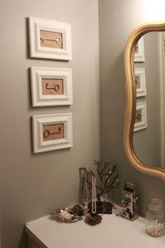 Vintage brass keys on burlap in white frames in the bathroom.
