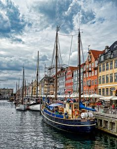 """< NYHAVN > Nyhavn (literally: New Harbour) is a 17th-century waterfront, canal and entertainment district in Copenhagen, Denmark. It is lined by brightly coloured 17th and early 18th century townhouses and bars, cafes and restaurants. Serving as a """"heritage harbour"""", the canal has many historical wooden ships."""