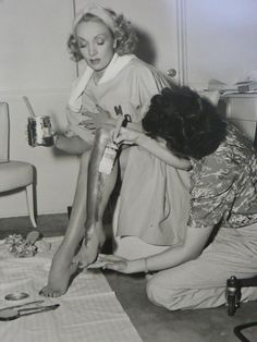 Marlene Dietrich has her famous legs painted for a scene of Kismet, 1944