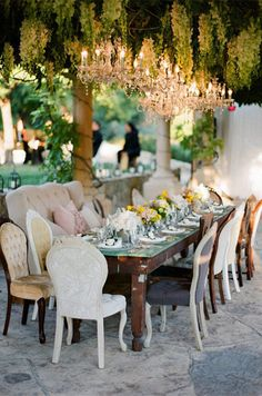 An eclectic reception tale is accented with a live ceiling and a multitude of crystal chandeliers. Garden Wedding Decor, Chandelier