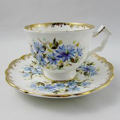 Gorgeous tea cup made by Aynsley. Cup and Saucer both have blue flowers. Gold trimming on cup and saucer edges, as well as on angular handle. Excellent condition (see photos). Markings read: Est 1775 Aynsley England Bone China 29 For more Aynsley tea cups, please click here: