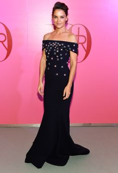 Katie Holmes is wearing a navy off shoulder Zac Posen gown with silver embellishments. Wow! Katie is gorgeous in this gown! Zac Posen is her signature designer! I love the silver embellishments against the navy color of the dress. It reminds me of stars in the dark sky.