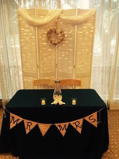 Sweetheart table backdrop : old bifold shutter doors, repurposed curtains for swag, burlap and lace heart shaped wreath. Behind, lots of twinkle lights, held in place with white duct tape.