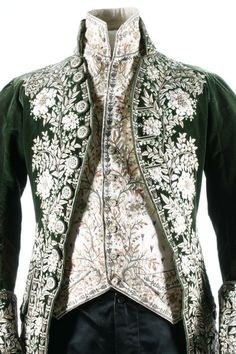 A gentleman's embroidered green velvet court coat and matching ivory satin waistcoat, French, circa 1790. heavily embellished with floss silk flowerheads and foliage; together with a pair of later black satin breeches