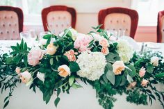 The head table was decorated with hydrangeas, roses, peonies, silver dollar eucalyptus, and greenery. Venue: Clay Hill Farm Floral Designer: York Flower Shop