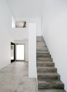 Concrete staircase + white walls.