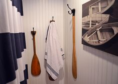 Kids' bathroom with nautical theme: navy ceiling, striped shower curtain, oars for towel hooks and boat print