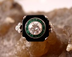 This is a gorgeous 14kt white gold Art Deco ring features black onyx, emerald, and diamonds. The center stone is a 1.45ct diamond with I1 clarity and H color. The center stone is surrounded by deep green emeralds and black onyx. There are also six auxiliary accent diamonds (three on each side). This ring has a flush top and would make a stunning engagement or anniversary ring. $7,700