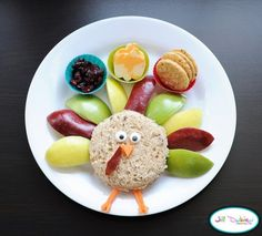 Turkey sandwich cut into circle shape. Icing eyes, carrot nose, and a red apple gobbly thingy. Sliced green, yellow, and red apples for the feathers. Carrot legs. 3 mini silicone cups filled with craisins, cheese pumpkins, and rice crackers.